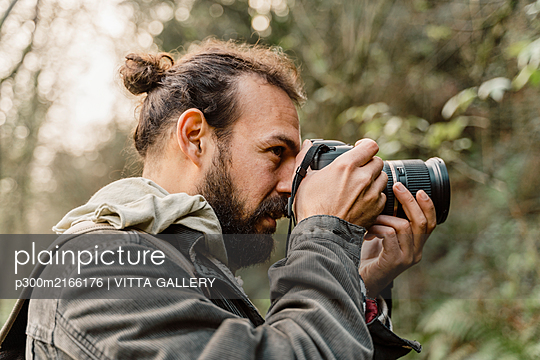 Young man taking pictures in the forest with his camera - p300m2166176 by VITTA GALLERY
