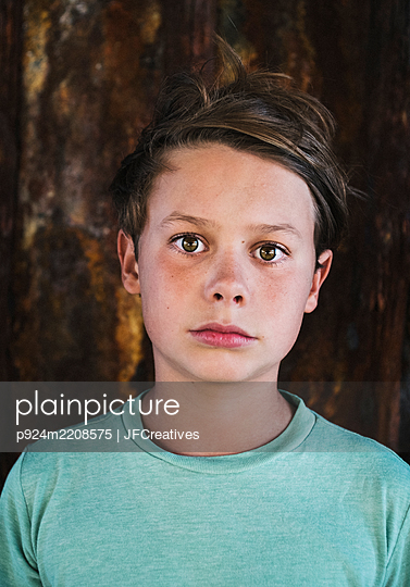 Portrait of boy with short brown hair, wearing green T-Shirt, looking at camera. - p924m2208575 by JFCreatives