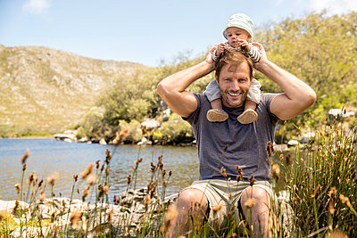 Father and baby on the lakefront - p1355m1574027 by Tomasrodriguez