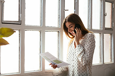 Happy young woman on cell phone looking at document at the window - p300m1587223 by Bonninstudio