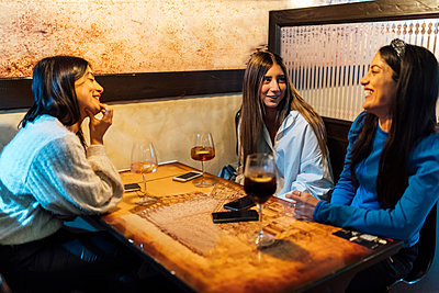 Female friends talking while having drinks in bar - p300m2242481 by Ezequiel Giménez