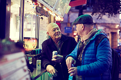 Senior gay couple standing against concession stand in city at night - p426m2165349 by Maskot