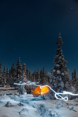 A trail of light leads past an orange tent in the middle of an snowy evergreen forest, snowshoes outside the tent, moonlight casting shadows on a clear winter night,  Interior Alaska; Gakona, Alaska, United States of America - p442m1217825 by Kevin Smith