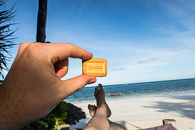 Man on the beach holding cookie - p930m1541582 by Ignatio Bravo