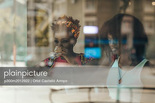Portrait of woman behind windowpane drinking glass of water - p300m2012922 von Oriol Castelló Arroyo