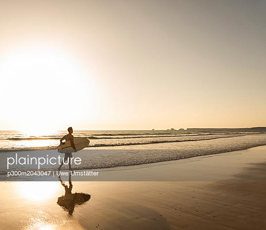 Young man running on beach, carrying surfboard - p300m2043047 von Uwe Umstätter