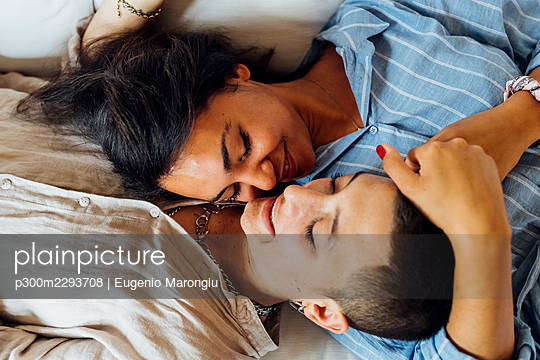 Affectionate young lesbian couple lying at home - p300m2293708 by Eugenio Marongiu