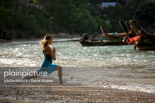 A young woman does yoga on a beach with longboats and sea stacks in Tonzai, Thailand. - p343m964915 by David Stubbs