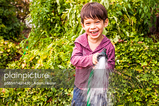 Mixed race boy playing with hose in garden - p555m1421430 by Adam Hester