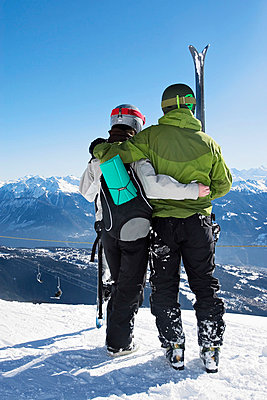 Rear view of a young couple standing with downhill skis and a snowboardan Alps - p3741842 by Juho Heikkinen