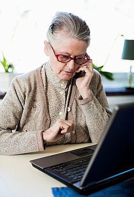 Senior woman using mobile phone while sitting with laptop on table - p426m844612f by Maskot
