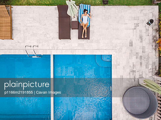 Aerial view of attractive woman near the pool at resort - p1166m2191855 by Cavan Images