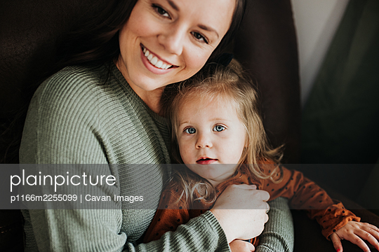 Young girl and her mother snuggle together on a chair in nursery - p1166m2255099 by Cavan Images