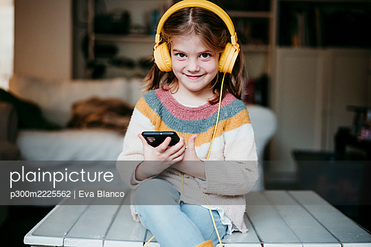 Smiling girl wearing headphones using mobile phone while sitting on table at home - p300m2225562 by Eva Blanco