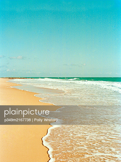 Incoming tide on Spanish beach under wide bright sky. - p349m2167738 by Polly Wreford