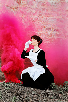 Maid drinking tea in pink smoke - p1521m2158312 by Charlotte Zobel