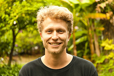 Portrait of smiling young strawberry blonde man - p300m2155901 by Tom Chance