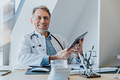 Male doctor using digital tablet while sitting at doctor's office - p300m2267718 by Mareen Fischinger