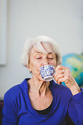 Senior woman with eyes closed having drink in nursing home - p426m2018705 by Maskot