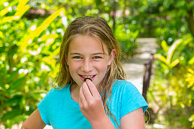 Caucasian girl eating snack - p555m1490992 by Marc Romanelli