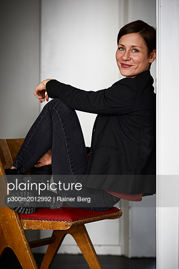 Modern woman crouching on chair, leaning on wall - p300m2012992 von Rainer Berg