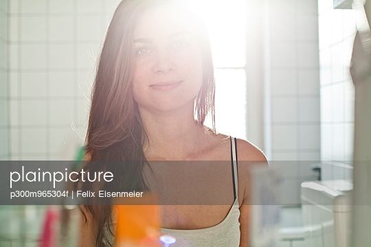 Portrait of smiling young woman looking at her mirror image at the bathroom - p300m965304f by Felix Eisenmeier