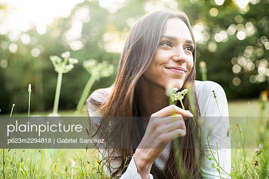Portrait of smiling young woman lying in park - p623m2294818 by Gabriel Sanchez
