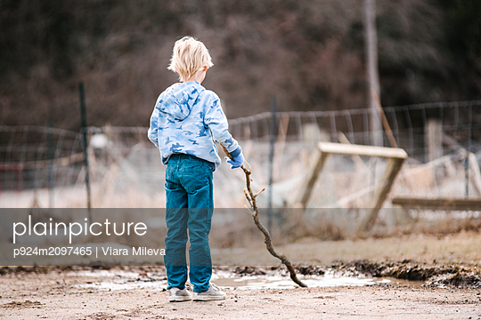 Blond boy on wasteland playing with tree branch in puddle, rear view - p924m2097465 by Viara Mileva