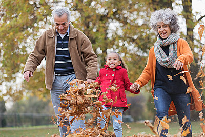 Playful grandparents and granddaughter kicking autumn leaves in park - p1023m2161195 by Tom Merton