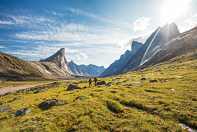 Distant rear view of two backpackers hiking through mountain pass. - p1166m2261207 by Cavan Images