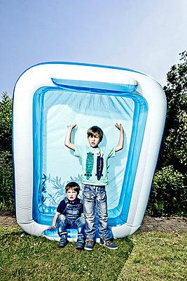 Zwei kleine Jungs stellen Planschbecken hoch - p1221m1041710 von Frank Lothar Lange