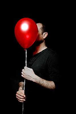 Man with a red balloon in front of his face - p1521m2150058 by Charlotte Zobel