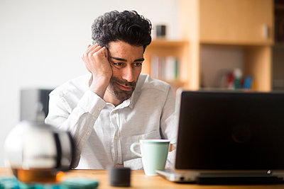 Portrait of businessman at desk looking at laptop - p300m1562355 by Sigrid Gombert