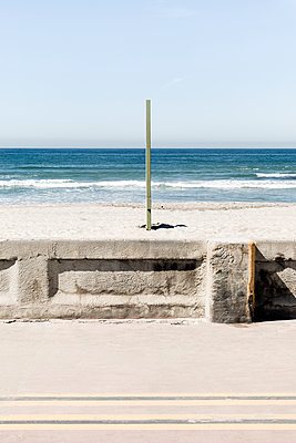 Wooden pole on sand at beach against clear sky - p1094m1467633 by Patrick Strattner