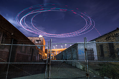 Low angle view of light paintings spinning over buildings at night - p1166m1519204 by Cavan Images
