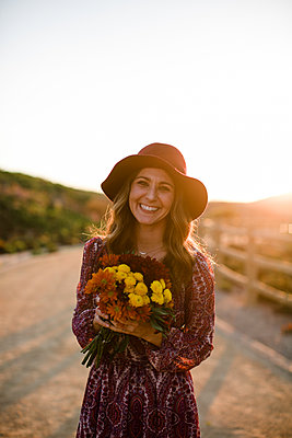Young woman holding flowers and smiling at camera at sunset in SoCal - p1166m2095787 by Cavan Images
