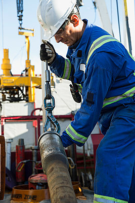 Male worker working drilling rig equipment gas plant - p1192m1127997f by Hero Images