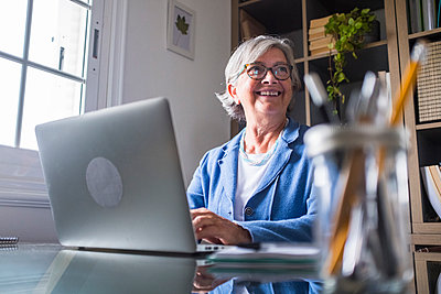 Happy businesswoman looking away while working with laptop at home - p300m2277629 by Simona Pilolla