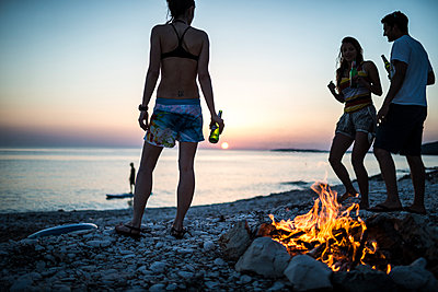 A group of young people gathered on a beach by a campfire. - p1100m1482333 by Mint Images