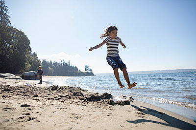 Exuberant girl jumping on sunny ocean beach - p1192m1511855 by Hero Images