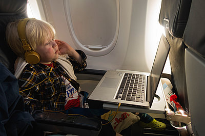 Little boy watching movie on computer i airplane - p1418m1590296 by Jan Håkan Dahlström