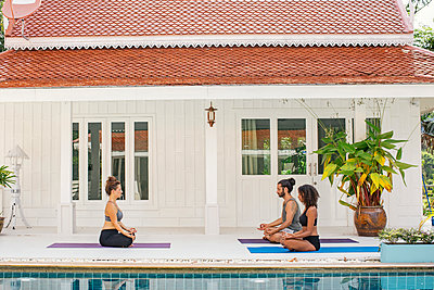 Two women and a man practicing yoga at the poolside - p300m1587011 by Mosu Media
