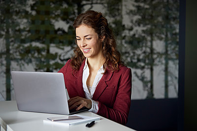 Smiling businesswoman using laptop in office - p300m2170870 by Rainer Berg