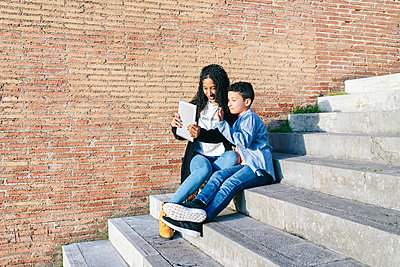 Mother and son sitting together on stairs taking selfie with digital tablet - p300m2188244 by Daniel González
