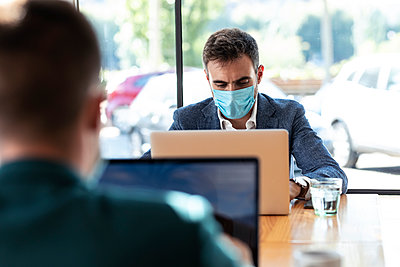 Businessman wearing protective face mask while using laptop in cafe during coronavirus outbreak - p300m2206791 by Josep Suria