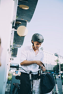 Smiling businessman with bicycle holding bags while standing in city - p426m2169595 by Maskot