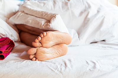 Bare feet under bedspread - p874m2182189 by Lisa Franz