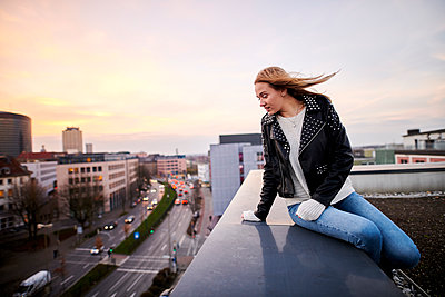 Young woman looking from rooftop onto city - p890m2231021 by Mielek