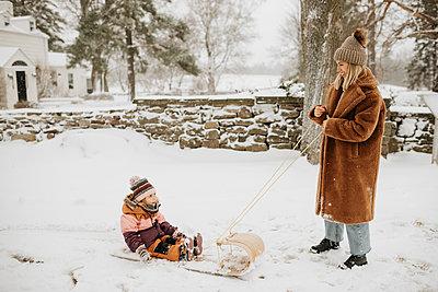 Canada, Ontario, Mother pulling daughter (2-3) on toboggan - p924m2271215 by Sara Monika