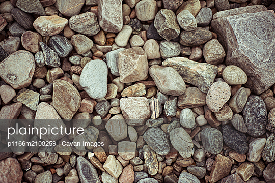 Flat lay birds eye of pretty pebbles and stones on beach - p1166m2108259 by Cavan Images